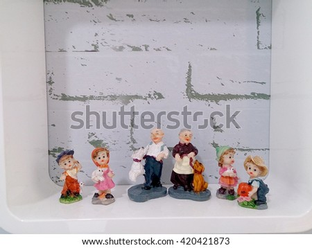 lovely grandparents with child ceramic dolls in white box on the wall
