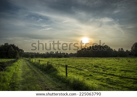Lovely green road heading for a wonderful sunset - stock photo