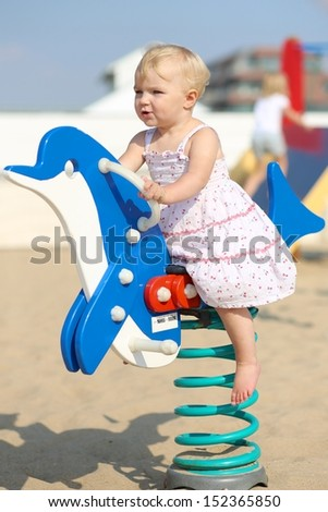 Lovely happy blond baby girl plays outdoor at the beach sandy playground rocking on a spring blue dolphin - stock photo