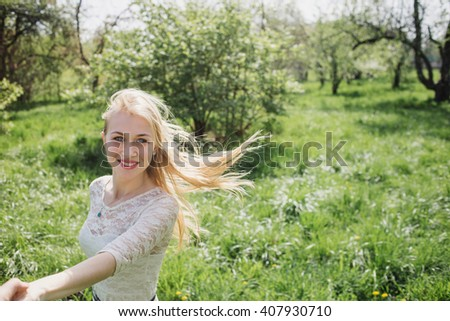 Lovely happy blonde  holding my hand  and dancing aroundin blossom garden. Point of view - stock photo