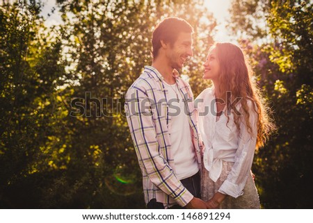 lovely happy couple looking to each other  at summer park - stock photo