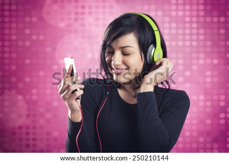 Lovely happy girl enjoying listening to music with headphones and mp3 player with eyes closed, smiling and dancing, isolated on pink disco background. - stock photo