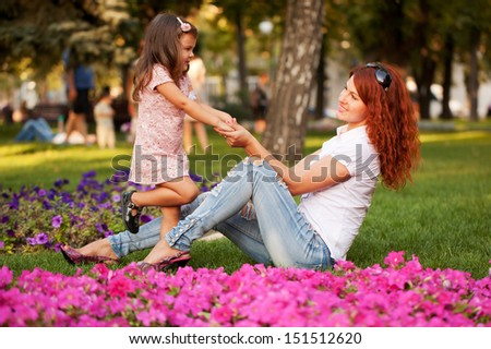 Lovely happy mother and daughter playing on the green grass in the park.