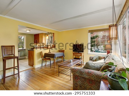 Lovely hardwood living room with yellow walls and colorful sofa.