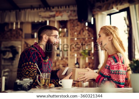 Lovely hipster couple enjoying sharing presents. Shallow depth of field.