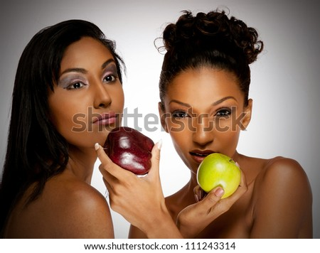 Lovely image of two beautiful women sharing apples with each other - stock photo
