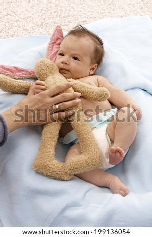 Lovely infant laying naked with plush bunny. - stock photo