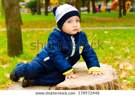Lovely kid sitting on a stump and looks into the distance pensively - stock photo