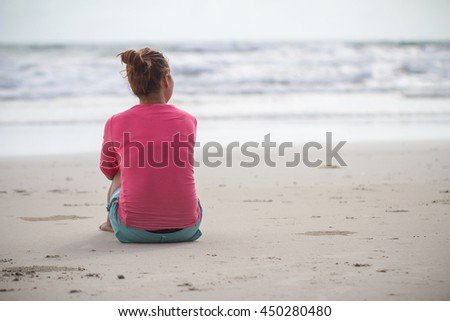 Lovely lady sitting alone on the sand. lonely lovelorn women sit on the beach.Style loneliness.divorce - stock photo