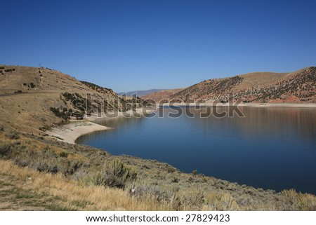 Lovely lake and blue sky contrasts with brown Utah hills.