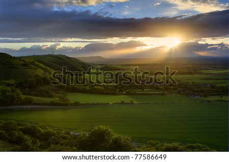 ... sun lighting up side of hills whit sun beams through dramatic clouds