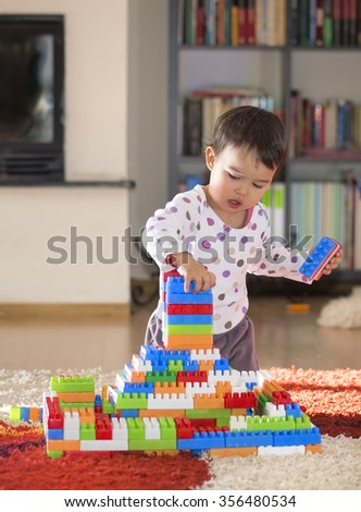 Lovely laughing little child,  playing with colorful blocks  - stock photo