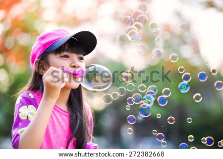 Lovely little asian girl blowing soap bubbles, Outdoor portrait - stock photo
