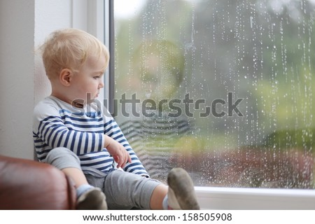 Lovely little baby girl looking outside through the window during the rain - stock photo