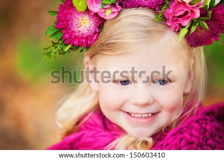 Lovely little baby girl with flowers on her head posing on a background of yellow leaves - stock photo