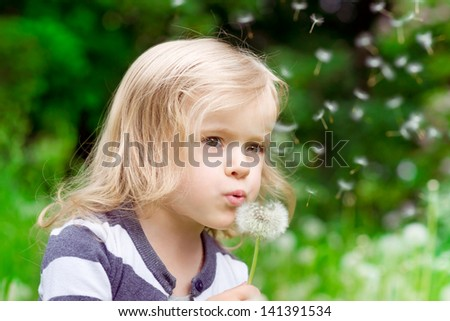 Lovely little blond little girl blowing a dandelion and making a wish in summer day - stock photo