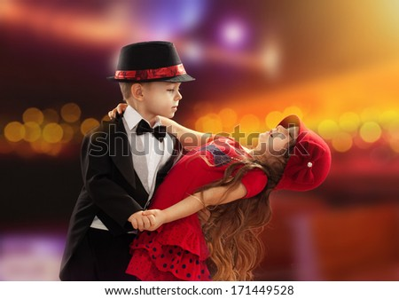 Lovely little boy and girl dancing in lights of the city - stock photo