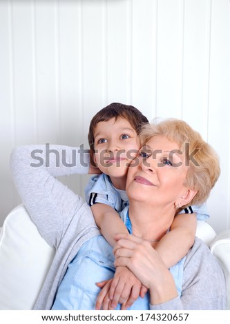 Lovely little boy with his grandmother having fun and happy moments together at home