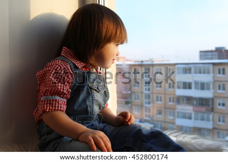 Lovely little boy (2 years) looks out of window - stock photo