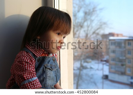 Lovely little boy (2 years) looks out of window in wintertime - stock photo