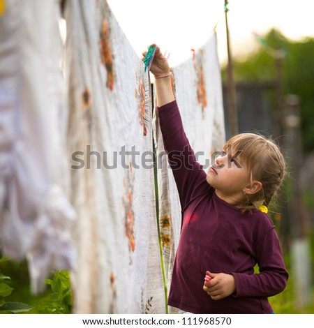 Lovely little five-year girl with clothespin outdoor - stock photo