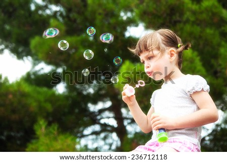 lovely little girl blowing soap bubbles - stock photo