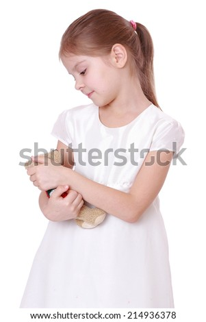 Lovely little girl hugging teddy bear on white background