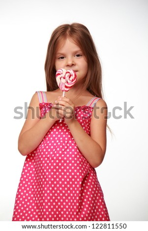 Lovely little girl is posing on camera with candy - stock photo