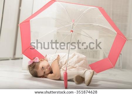 Lovely little girl lying down on the floor under an umbrella, indoor shot on white room - stock photo