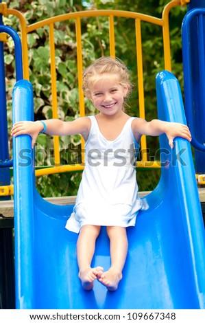 lovely little girl on a children's slide - stock photo
