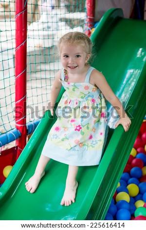 lovely little girl on a children's slide on playground - stock photo