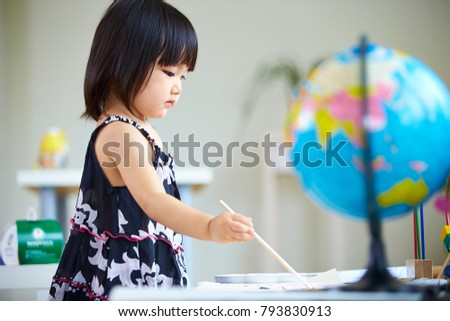 lovely little girl painting in home