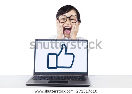 Lovely little girl screaming on the camera with OK sign on the laptop screen, isolated on white - stock photo