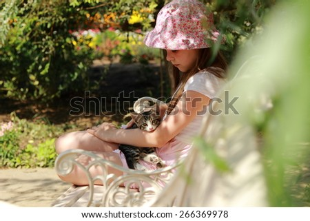 Lovely little girl sitting on the bench in park - stock photo