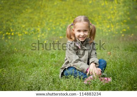 Lovely little girl sitting on the grass - stock photo