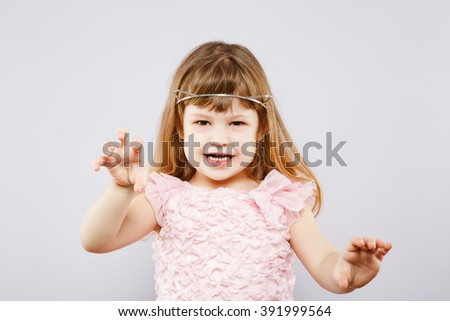 Lovely little girl wearing pink dress and metal cat ears and posing like tiger, looking at camera, gray studio background, copy space, portrait. - stock photo