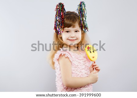 Lovely little girl wearing pink dress, festoon ears and holding candy, looking at camera, gray studio background, copy space, portrait, smiling. - stock photo