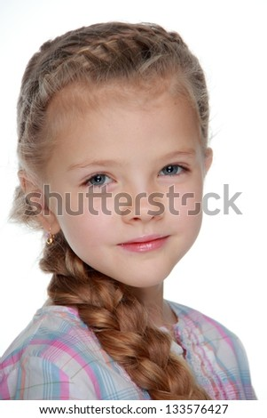 Lovely little girl with a long braid poses for the camera and smiling