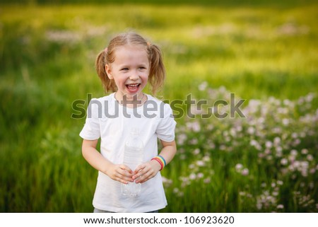 Lovely little girl with flushed cheeks because of having a lot of run standing with the bottle of water outdoors - stock photo