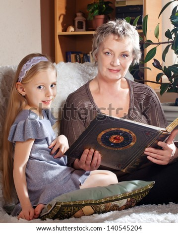 Lovely little girl with her grandmother reading book - stock photo