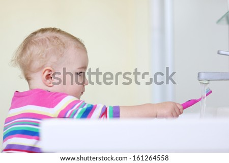 Lovely little toddler girl cleaning tooth brush after brushing her teeth - stock photo