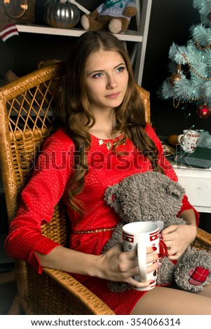 Lovely,long-haired,thinking,looking aside,holding a little,grey,nice teddy bear,cup of tea,coffee,milk,chocolate,red dress,sitting in the big wicker chair girl,winter,new-year's,christmas,photo studio - stock photo