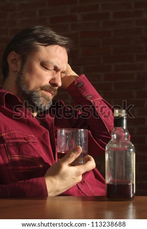 Lovely man sits quietly at his home at the table - stock photo