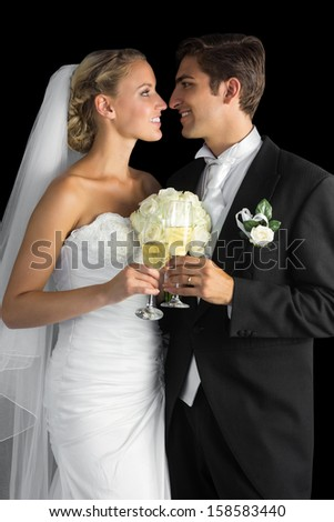 Lovely married couple posing holding champagne glasses looking at each other - stock photo