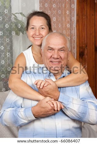 Lovely mature couple poising on sofa at home