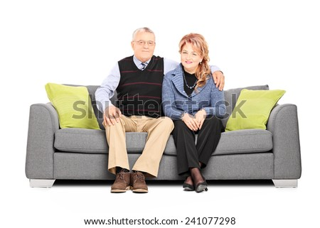 Lovely mature couple posing seated on sofa isolated on white background - stock photo