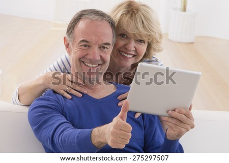 lovely mature couple using tablet computer at home
