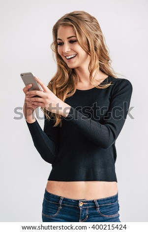 Lovely message from friend. Beautiful young woman using her smartphone with smile while standing against white background - stock photo