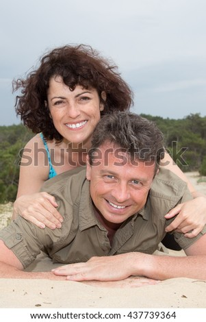 Lovely middle-aged couple smiling at the beach on sand