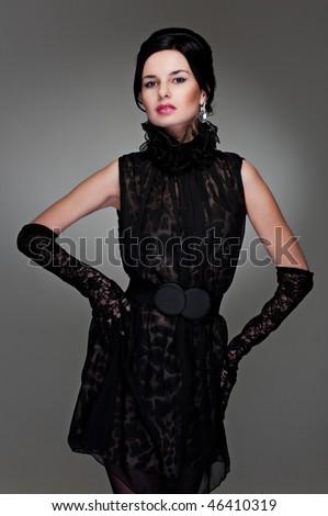 lovely model in evening dress posing against dark background - stock photo